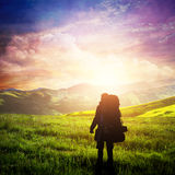 Man with backpack trekking on highlands. Fantastic sunset sky, summer adventure. Royalty Free Stock Image