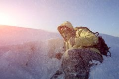 Man with backpack trekking in mountains. Cold weather, snow on hills. stock photo