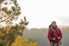 Man with backpack and trekking pole in bandana standing on a roc Stock Image