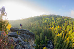 Man with backpack and trekking pole in bandana standing on a rock at dawn on a background autumn forest stock photos