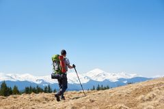 Male hiker with backpack in the mountains. Man with a backpack and trekking sticks hiking in the mountains copyspace landscape view beauty achievement success Royalty Free Stock Photo
