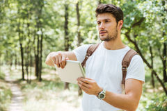 Man with backpack using tablet outdors. Serious young man with backpack using tablet outdors Royalty Free Stock Photo