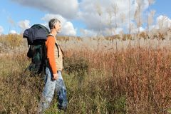 Man with a backpack walking across a field with tall grass Stock Images