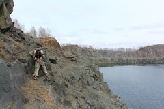 Man walking along the steep bank of a flooded quarry. Man with a backpack walking along the steep bank of a flooded quarry, Toguchinsky district, Siberia, Russia stock photography