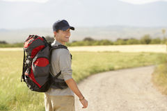 Man With Backpack Walking On Country Road Stock Photos