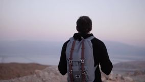 Man with backpack walking in dusk desert wilderness. Slow motion. Male wanders alone looking at scenic sunset sky. Israel. Meditation and reflection retreat stock footage