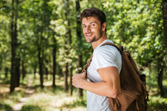 Man with backpack walking in forest. Happy young man with backpack walking in forest Royalty Free Stock Photography