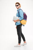 Man with backpack walking and holding laptop. Cheerful young man with backpack walking and holding laptop Stock Image