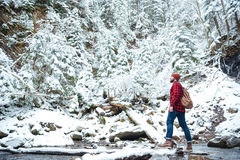Man with backpack walking near the river in winter forest. Handsome bearded young man in checkered shirt with backpack walking near the river in winter forest Royalty Free Stock Photography