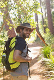 Man with backpack walking on the path in forest Stock Photography