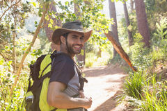 Man with backpack walking on the path in forest Royalty Free Stock Images
