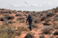 Man with backpack walks on deserted land Stock Images