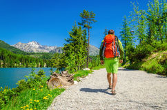Man with backpack walks mountain trail by lake Royalty Free Stock Images