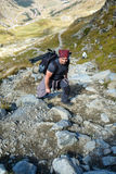Man backpacker hiking on a trail. Man hiker with backpack walking a trail in rocky mountains Royalty Free Stock Photo