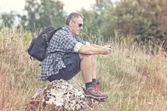 Backpacker sitting on a rock Royalty Free Stock Photos