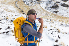 Man backpacker tourist using lipstick, Condoriri mountains Bolivia. Royalty Free Stock Photos