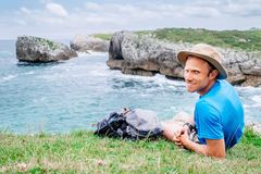Man backpacker traveler rests on the rocky sea side, looks in ca. Mera and smile Royalty Free Stock Images
