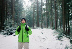 Man backpacker walking in winter mountain forest Stock Photos