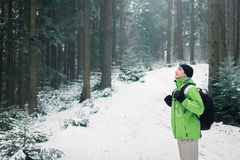 Man backpacker walking in winter mountain forest Stock Photography