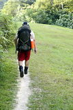 Man backpacking outdoors. Man backpacking on worn path outdoors Stock Image