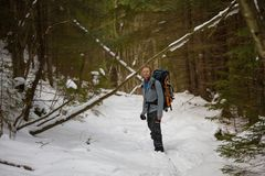 Man is backpacking in winter forest Royalty Free Stock Images
