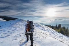 Man is backpacking in winter mountains Stock Photos