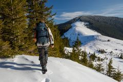 Man is backpacking in winter mountains Royalty Free Stock Photo
