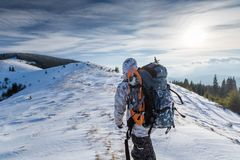 Man is backpacking in winter mountains Royalty Free Stock Image