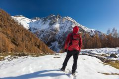 Man is backpacking in winter mountains. Piemonte, Italian Alps,. Europe royalty free stock photography