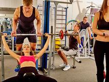 Man backs girl taking exercises at gym. Group people background. Woman working his arms and chest at gym. She lifting barbell. Man backs girl while taking royalty free stock images