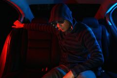 Man in the backseat of a car wearing a hoodie shirt Royalty Free Stock Images