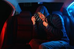 Man in the backseat of a car wearing a hoodie shirt Royalty Free Stock Photography