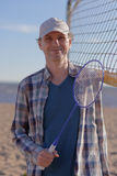 Man with badminton racket on a beach Stock Image