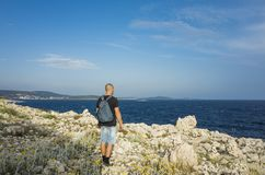 Man with bag on back standing on rocky coast line in Croatia close sea Royalty Free Stock Image