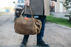 The man with a bag goes to a coat to the house. Stock Photography
