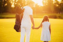 Man with a bag for golf clubs and a girl walking along a golf course holding hands on a sunset background Stock Image