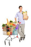 Man with bag next to a shopping cart. Full length portrait of a man with paper bag next to a shopping cart full with groceries on white background royalty free stock images