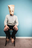 Man with bag over head on chair. A Man with a paper bag over his head is sitting on a chair against a blue wall Stock Photos