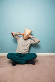 Man with bag over head on floor covering ears Royalty Free Stock Image