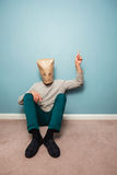 Man with bag over head on floor is pointing Royalty Free Stock Images