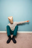 Man with bag over head on floor is pointing Stock Image