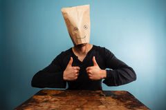 Man with bag over head giving thumbs up Royalty Free Stock Image