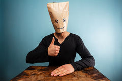 Man with bag over head giving thumbs up Stock Photo