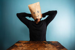 Man with bag over head relaxing at desk. Man with bag over his head relaxing at desk Royalty Free Stock Photo
