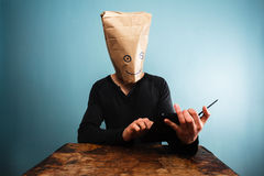 Man with bag over head using tablet computer Royalty Free Stock Photo