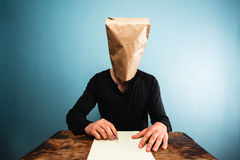 Man with bag over head writing letter Royalty Free Stock Photography