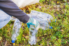Man with bag picking up used plastic bottles Royalty Free Stock Photo