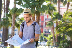 Man with bag on vacation looking at map Royalty Free Stock Image