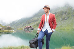 Man with bag walking near mountain lake with cabin Royalty Free Stock Image