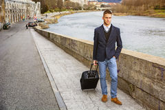 Man with baggage standing on pavement near river. Young man in trendy clothes with baggage standing on pavement near river while looking away Royalty Free Stock Photography